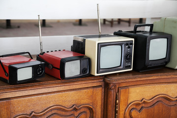 Row of portable vintage TV sets with selective focus
