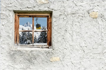 Winterlandschaft mit Bergbahn im Fenster