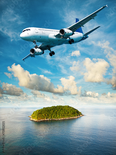 Jet is maneuvering over the tropical island - 70802835