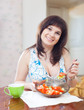 woman eats veggie salad on sofa at  interior