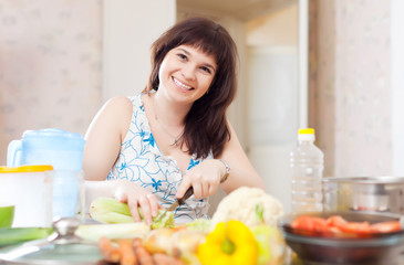 Positive  woman cutting the celery