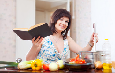 Young housewife cooking with cookery book
