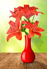 Red lily flowers in the red vase