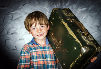 Emotional red-haired boy with suitcase