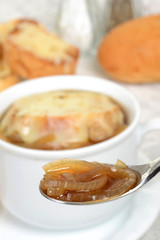 spoon of french onion soup shallow DOF