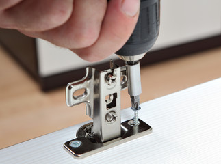 Furniture assembly, installation of door hinges, screws screwed