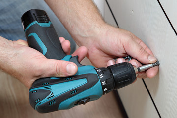 Using cordless screwdriver for screwing screws when assembling f