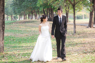 Bride and groom holding hand and walk in the garden