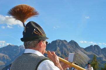 Alphornspieler mit Hut im Gebirge