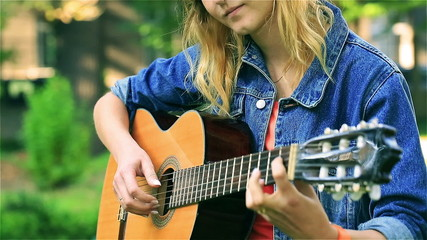 Pretty girl in the park playing on the guitar, steadycam shot