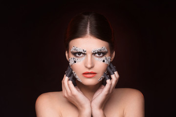 Beautiful woman with crystals makeup keep her hands near face