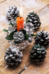 Christmas candle is decorated with pine cones and snow