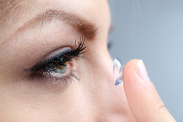 Medicine and vision concept - young woman with contact lens,