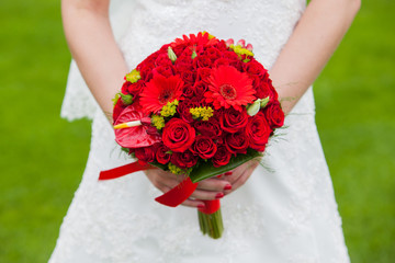 Bride with red wedding bouquet in hand