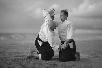 Aikido masters practicing on the beach; monochrome