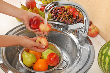 Woman's hands washing peaches and other fruits in colander in