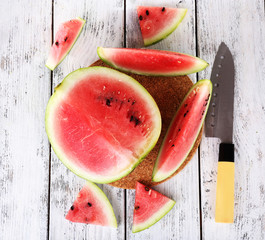 Watermelon and knife on cutting board on wooden background