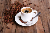 Fototapety Cup of coffee and coffee beans on wooden background