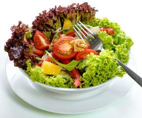 gemischter Salat mit Gabel auf weißem Untergrund