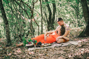 Pregnant woman with her husband having picnic in a forest