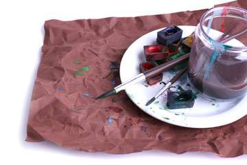 Watercolor paint cubes with brushes and jar with water