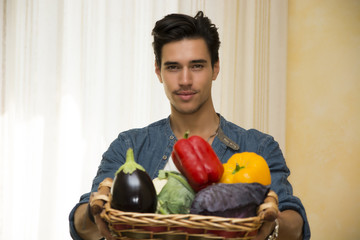 Young man holding a basket of fresh vegetables