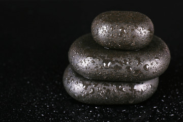Spa stones with drops isolated on black