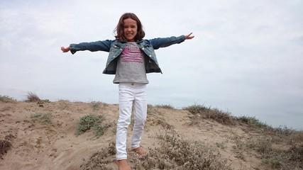 Niña descalza sobre duna de playa