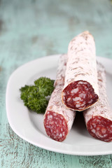Italian salami on plate,  on wooden background