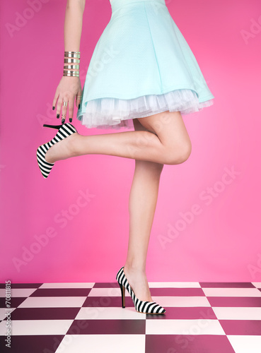 canvas print picture Young woman standing on one leg wearing high heels
