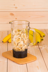 Mixer with banana slices and fruits.