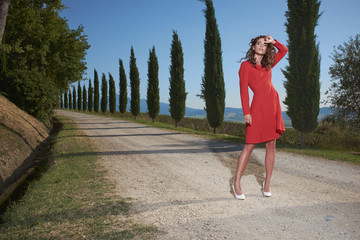 A woman in a red dress on the road in Tuscany