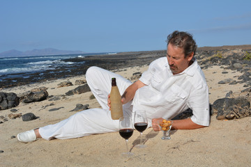 A man with a bottle of wine and two glasses on the beach