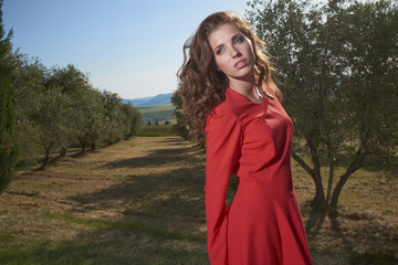 Woman in red dress among the olive trees