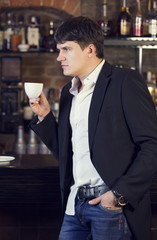 man drinking coffee near the bar