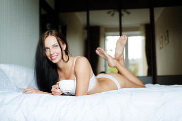 Young woman with a cup in a bed