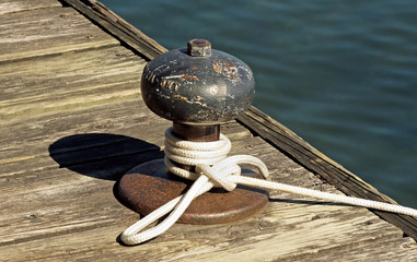 Rope tied to a metal boat slip at dock