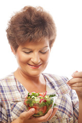 Mature smiling woman eating salad
