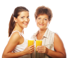 Two women with orange juice. Mother and Daughter.