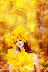 Young beautiful girl with autumn leaves in his hand, and the wre