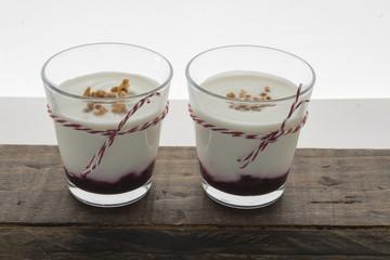 Layered dessert with fruits yogurt and cream cheese in glass jar