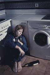 drunk alcoholic woman sitting on kitchen floor drinking wine