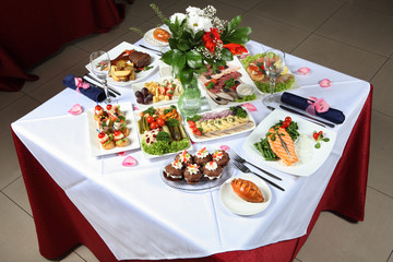 Laid table with a variety of dishes, fish, pastries, pickles