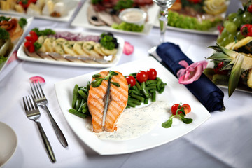 Grilled salmon steak with green beans, on decorated dining table