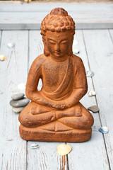 bruine boeddha met strand decoratie op oud hout