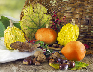 Pumpkins and autumn fruits with basket on wooden table