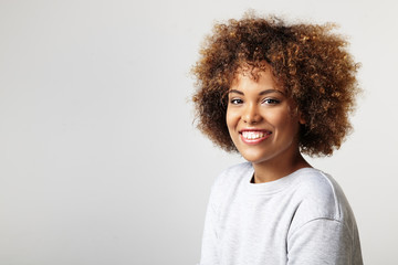portrait of a latin woman with a curly hair, wearing sweatshirt