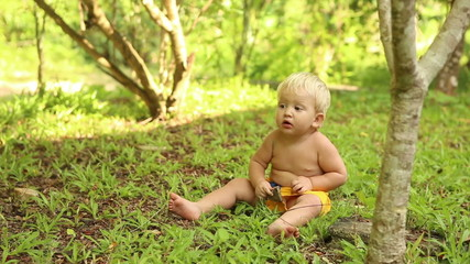 white baby in yellow chert sitting on the grass and digging