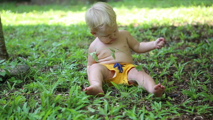 white baby in yellow chert sitting on the grass and exploring