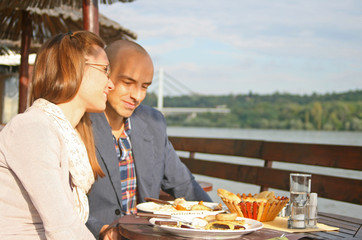 Romantic couple smiling at lunch by the river- sunny day